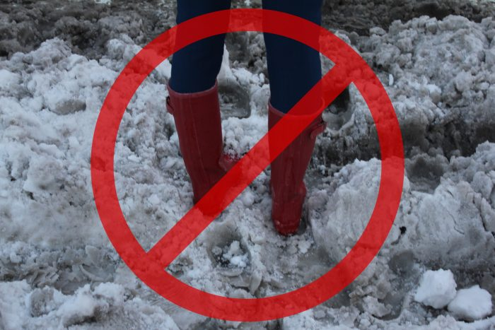 Woman's legs standing in slushy snow with a red prohibited symbol superimposed on top